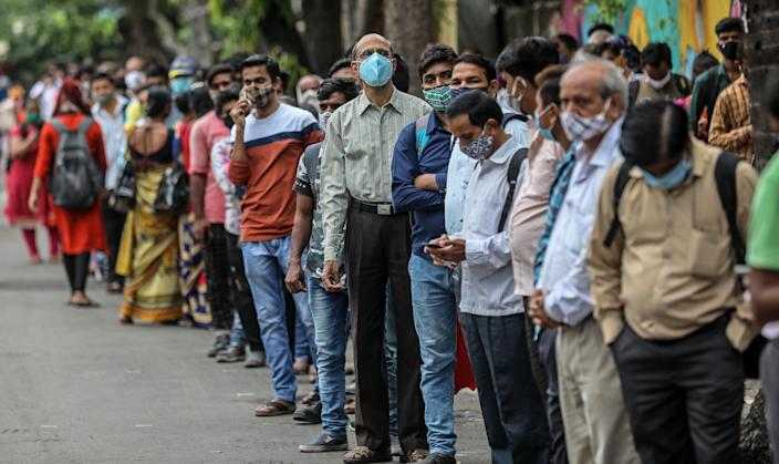 <p>People stand in a queue as they wait for public transport at a bus stop in Mumbai, India, on 8 June, 2021</p> (EPA)