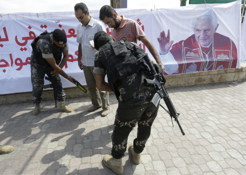 Lebanese Army soldiers search citizens outside Rafik Hariri international airport during a security measure, in Beirut, Lebanon, Friday Sept. 14, 2012. Pope Benedict XVI is expected to arrive in Lebanon for a three day visit to encourage his flock in the Middle East. He will also meet with Lebanese authorities as well as Christians from Lebanon and other nearby countries.(AP Photo/Hussein Malla)