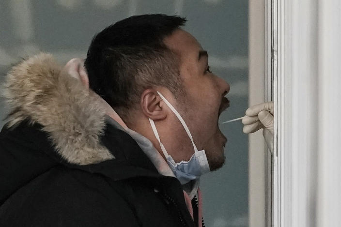 A man gets a swab for the coronavirus test at a hospital in Beijing, Sunday, Jan. 17, 2021. The coronavirus was found on ice cream produced in eastern China, prompting a recall of cartons from the same batch, according to the government. (AP Photo/Andy Wong)