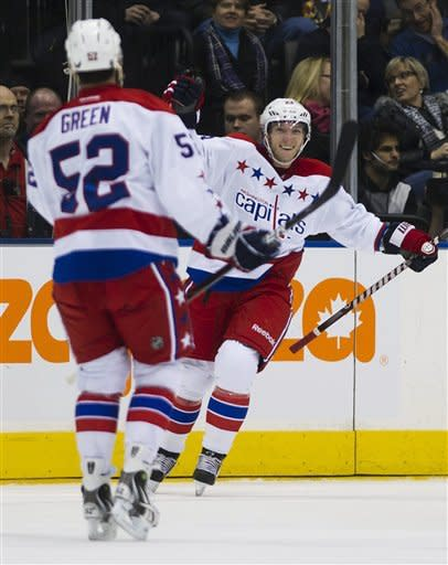 Washington Capitals' Keith Aucoin, right, celebrates his first goal of the season with teammate Mike Green, left, while playing against the Toronto Maple Leafs during second-period NHL hockey game action in Toronto, Saturday, Feb. 25, 2012. (AP Photo/The Canadian Press, Nathan Denette)