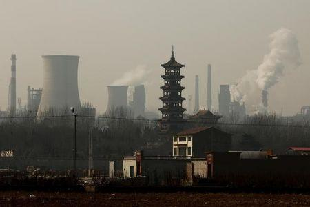 Cooling towers emit steam and chimneys billow in an industrial zone in Wu'an