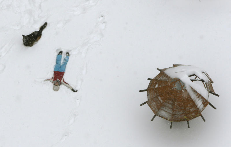 A woman and her dog enjoy snowfall in Kiev, Ukraine, Saturday, March 23, 2013. Heavy snow storms from the Balkan region have been stricken Ukraine since last afternoon, in the last winter attack at the end of the first spring month. (AP Photo/Efrem Lukatsky)