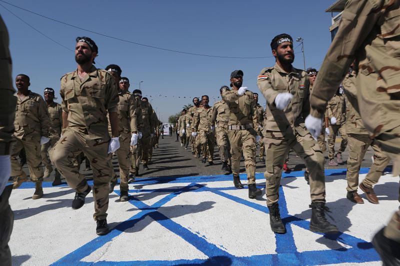 """Iraqi Popular Mobilization Forces march over a representation of an Israeli flag during """"al-Quds"""" Day, Arabic for Jerusalem, in Baghdad, Iraq, Friday, May 31, 2019. Jerusalem Day began after the 1979 Islamic Revolution in Iran, when the Ayatollah Khomeini declared the last Friday of the Muslim holy month of Ramadan a day to demonstrate the importance of Jerusalem to Muslims. (AP Photo/Khalid Mohammed)"""