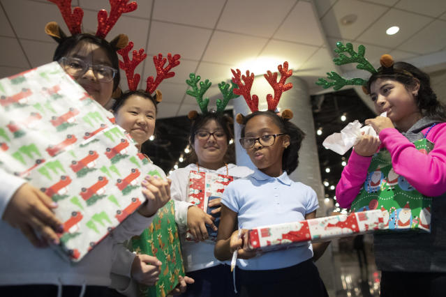Children show off the gifts they received during the New York Mets annual Kids Holiday Party, Wednesday, Dec. 4, 2019, in New York. (AP Photo/Mary Altaffer)