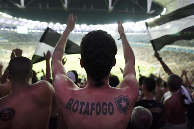 In this April 2, 2014 photo, fans of the Botafogo soccer team react during a Copa Libertadores game at Maracana stadium in Rio de Janeiro, Brazil. Soccer's big moment happens in June as the best players on the planet meet in Brazil for the World Cup. The international soccer tournament will be the first in the South American nation since 1950. (AP Photo/Leo Correa)