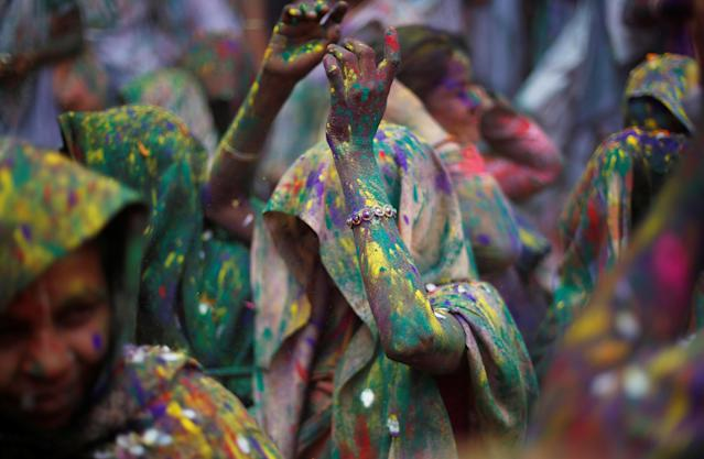 <p>Widows daubed in colours dance as they take part in Holi celebrations in the town of Vrindavan in the northern state of Uttar Pradesh, India, Feb. 27, 2018. (Photo: Adnan Abidi/Reuters) </p>