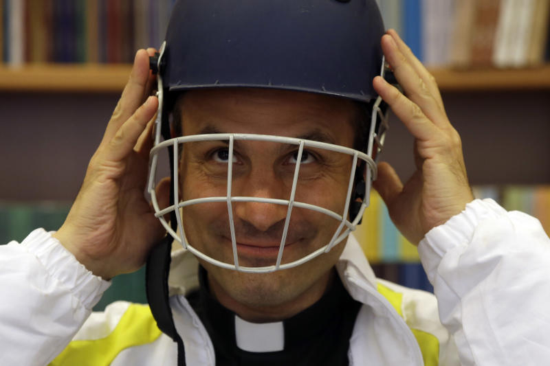 """Monsignor Sanchez de Toca y Alameda, undersecretary of the Pontifical Council for Culture, wears a cricket helmet during the presentation of the Vatican cricket club at the Vatican, Tuesday, Oct. 22, 2013. The Vatican has officially launched its cricket club, an initiative aimed at forging ties with teams of other faiths. Pope Francis marked the occasion by having tea and cucumber sandwiches served for a sport long associated with manicured grounds and English nobility. But the soccer-mad """"slum pope"""" still prefers that lower-brow sport. He and the Vatican have long championed sports as good for the mind, body and soul. The cricket club is the latest initiative of the Vatican's culture ministry to use sports to engage in dialogue with the contemporary world. (AP Photo/Gregorio Borgia)"""