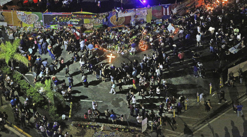 FILE - In this June 12, 2017, file photo, people gather at the Pulse nightclub in Orlando, Fla., on the first anniversary of the mass shooting there. In the five years since a gunman killed 20 children and six adults at the Sandy Hook elementary school in Newtown, Conn., the nation has seen a number of massacres topping the death toll from that shooting. But Americans wanting to know why mass shootings are happening will get few answers. (Red Huber/Orlando Sentinel via AP, File)