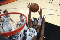 Milwaukee Bucks forward Giannis Antetokounmpo (34) reaches for the ball during the first half against the Phoenix Suns in Game 5 of basketball's NBA Finals, Saturday, July 17, 2021, in Phoenix. (Mark J. Rebilas/Pool Photo via AP)
