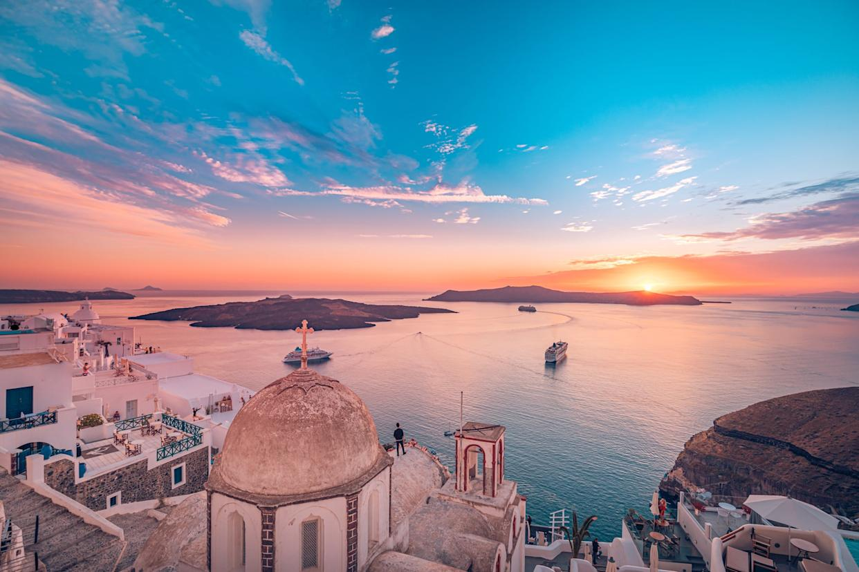 Amazing evening view of Fira, caldera, volcano of Santorini, Greece with cruise ships at sunset. Cloudy dramatic sky