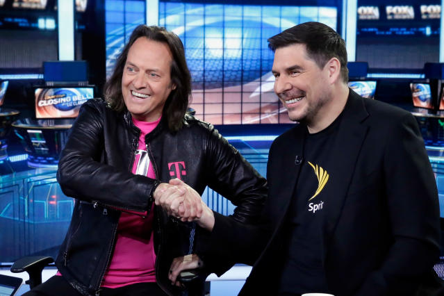 """T-Mobile CEO John Legere, left, and Sprint CEO Marcelo Claure shake hands as they are interviewed by Liz Claman during her """"Countdown to the Closing Bell"""" program on the Fox Business Network, in New York, Monday, April 30, 2018. (AP Photo/Richard Drew)"""