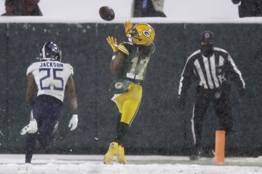 Green Bay Packers' Davante Adams catches a touchdown pass in front of Tennessee Titans' Adoree' Jackson during the first half of an NFL football game Sunday, Dec. 27, 2020, in Green Bay, Wis. (AP Photo/Matt Ludtke)