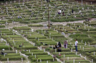 People visit the graves of family members at the special section of a cemetery allocated for the victims of COVID-19 in Medan, North Sumatra, Indonesia, Monday, Jan. 25, 2021. Indonesia has reported more cases of the virus than any other countries in Southeast Asia. (AP Photo/Binsar Bakkara)