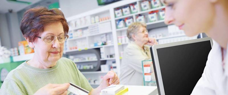 Customer paying by credit card at drug store