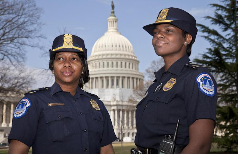 "Officers Yogananda ""Yogi"" Pittman, left, and Monique Moore, right, the first two African-American women to be promoted to the rank of captain on the U.S. Capitol Police force, stand together on the East Lawn of the Capitol in Washington, Monday, March 19, 2012. (AP Photo/J. Scott Applewhite)"