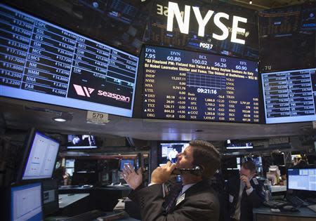 A trader looks up at a screen on the floor of the New York Stock Exchange at the market open in New York, October 14, 2013. REUTERS/Carlo Allegri