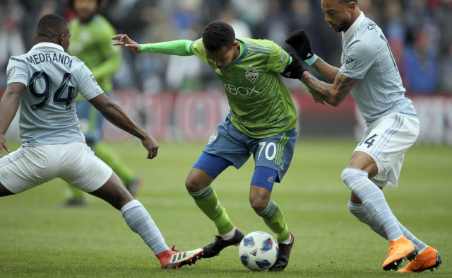 Seattle Sounders forward Handwalla Bwana (70) works between Sporting Kansas City midfielder Jimmy Medranda (94) and forward Khiry Shelton (14) during the first half of an MLS soccer match in Kansas City, Kan., Sunday, April 15, 2018. (AP Photo/Orlin Wagner)
