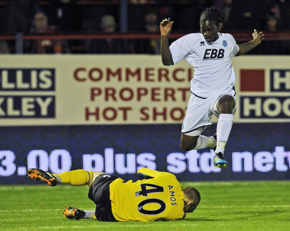 Aldershot Town's Jermaine McGlashan, right, leaps over Manchester United''s Ben Amos during their English League Cup soccer match at the EBB stadium, Aldershot, south of London, Tuesday, Oct. 25, 2011. (AP Photo/Tom Hevezi)