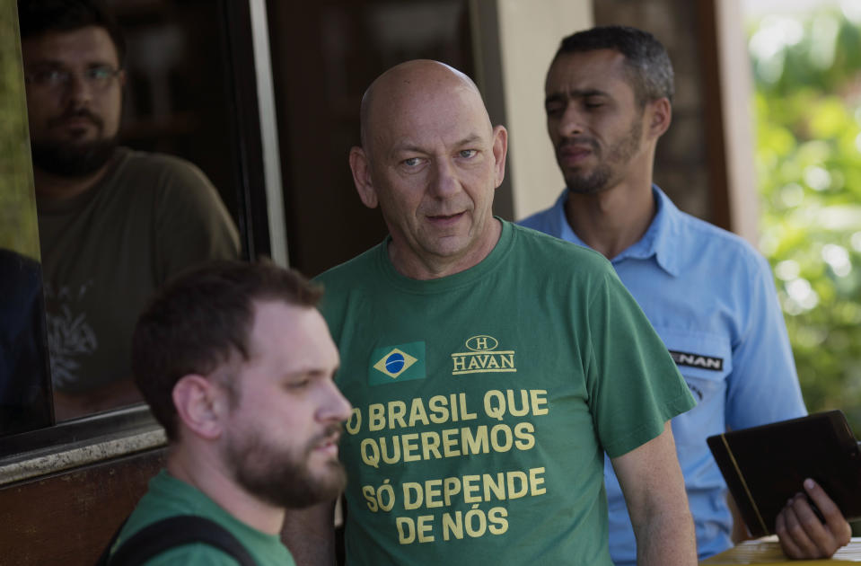"""Brazilian entrepreneur Luciano Hang waits to be authorized to enter and visit presidential candidate Jair Bolsonaro, of the Social Liberal Party, in Rio de Janeiro, at Bolsonaro's home in Rio de Janeiro, Brazil, Wednesday, Oct. 10, 2018. His shirt reads in Portuguese: """"The Brazil we want just depends on us."""" (AP Photo/Leo Correa)"""