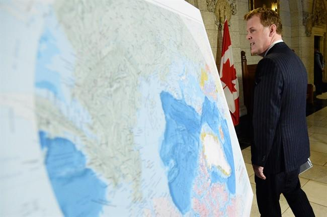Foreign Affairs Minister John Baird walks past a map of the Arctic at a news conference on Canada's Arctic claim in Ottawa, Monday, Dec.9, 2013. THE CANADIAN PRESS/Sean Kilpatrick