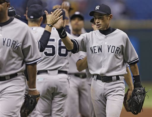 New York Yankees' Ichiro Suzuki, of Japan, right, high fives teammates after the Yankees defeated the Tampa Bay Rays 4-3 during a baseball game Tuesday, April 23, 2013, in St. Petersburg, Fla. Suzuki hit a two-run single off Tampa Bay Rays relief pitcher Fernando Rodney. (AP Photo/Chris O'Meara)