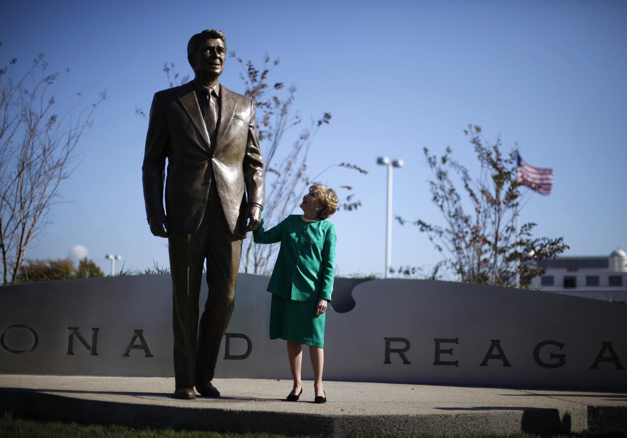 Elizabeth Dole, former Secretary of Transportation under former U.S. President Ronald Reagan, holds onto a newly-unveiled statue of Reagan at Ronald Reagan National Airport near Washington November 1, 2011. The statue is one of several worldwide that are being unveiled in 2011 as part of the historic year-long celebration commemorating the 100th anniversary of Reagan's birth.  (REUTERS/Jason Reed)