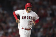 Los Angeles Angels designated hitter Shohei Ohtani pulls gloves for baserunning after drawing an intentional walk during the sixth inning of the team's baseball game against the Detroit Tigers in Anaheim, Calif., Saturday, June 19, 2021. (AP Photo/Kyusung Gong)