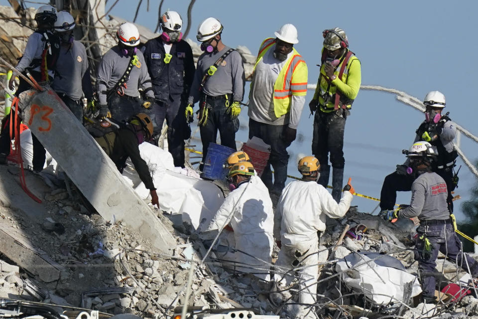 A team secures sets of recovered remains in body bags, as search and rescue personnel work atop the rubble at the Champlain Towers South condo building where scores of people remain missing more than a week after it partially collapsed, Friday, July 2, 2021, in Surfside, Fla. Rescue efforts resumed Thursday evening after being halted for most of the day over concerns about the stability of the remaining structure.(AP Photo/Mark Humphrey)