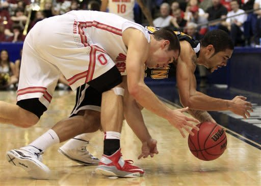 Ohio State guard Aaron Craft, left, chases a loose ball with Iona guard Tre Bowman in the first half of a second-round game at the NCAA college basketball tournament, Friday, March 22, 2013, in Dayton, Ohio. (AP Photo/Skip Peterson)