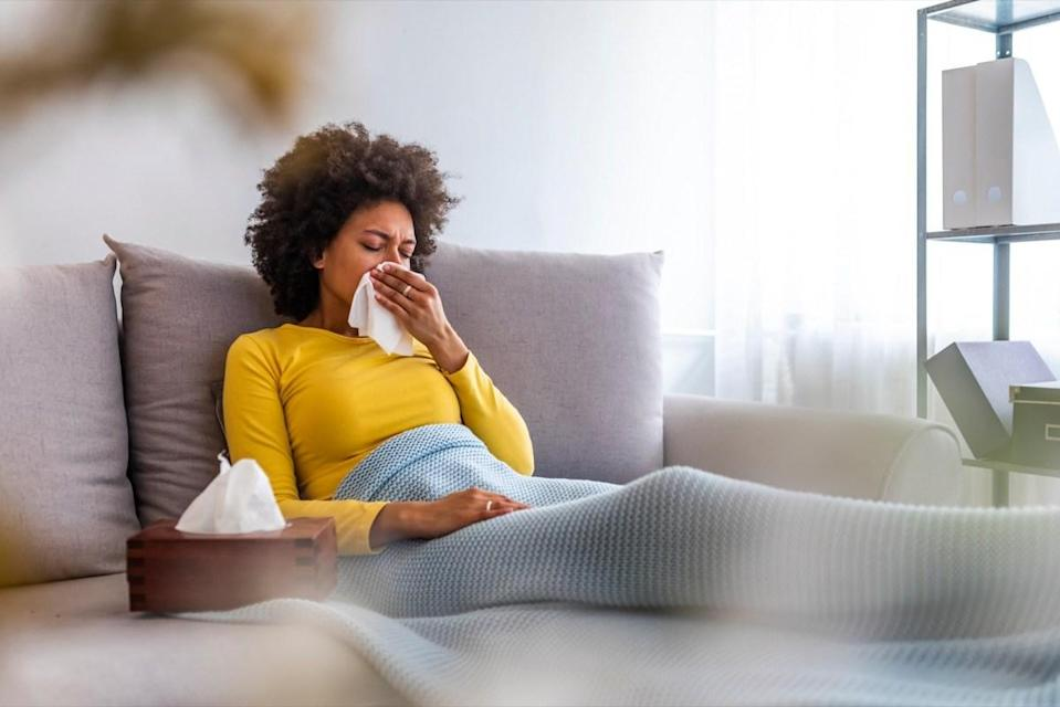Woman sneezing in a tissue in the living room. Woman blowing her nose on couch at home in the living room. African American woman using a tissue sitting on a sofa at home
