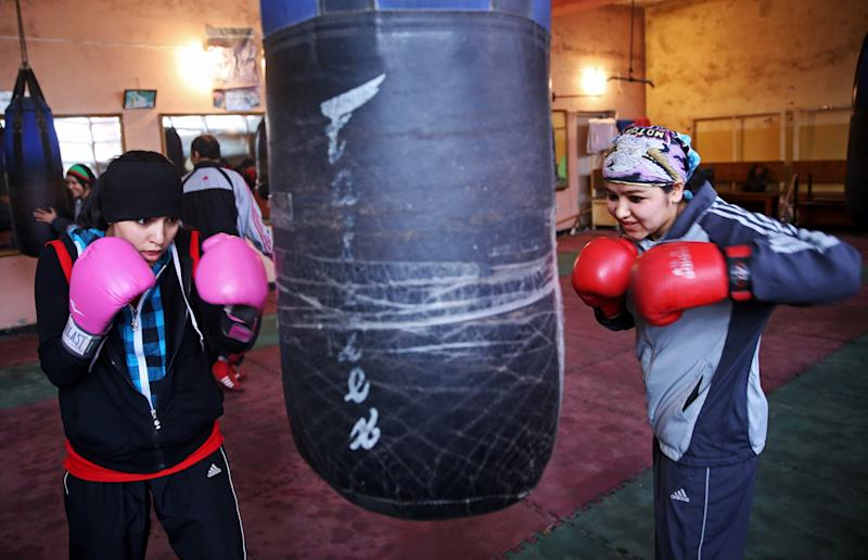 In this Wednesday, March, 5, 2014 photo, Afghan women boxers practice at the Kabul stadium boxing club. A few yellow lamps light up the cavernous, sparsely furnished room where Afghanistan's young female boxers train, hoping to become good enough to compete in the 2016 Olympics. (AP Photo/Massoud Hossaini)