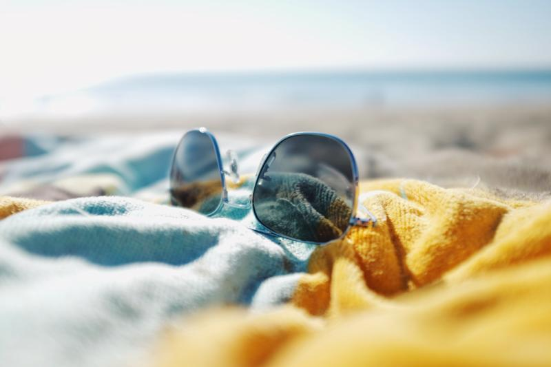 Sunglasses laying on colourful beach towel on sandy beach in summer