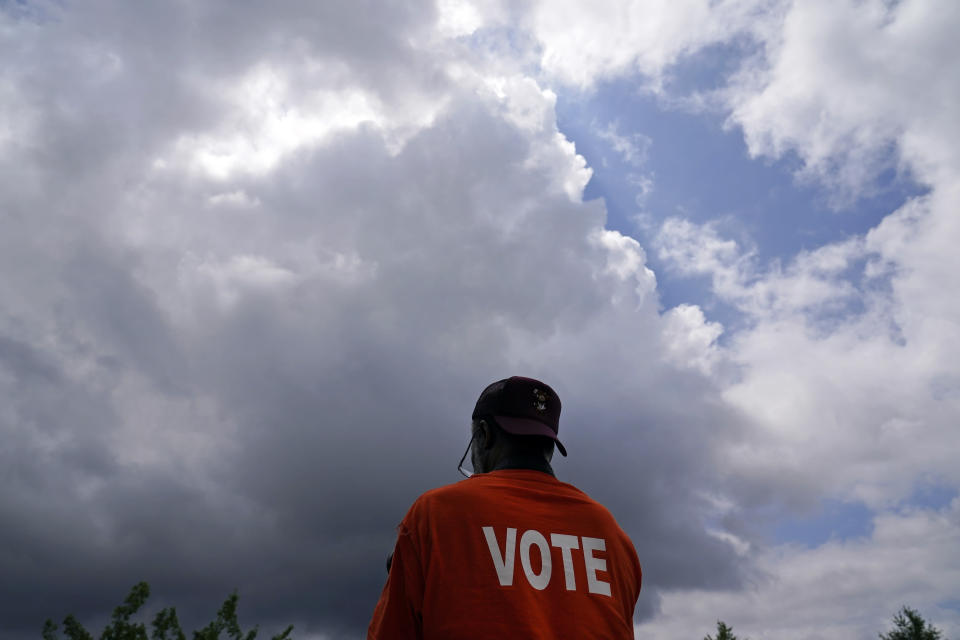 A person listens to prayer during a voting rights rally at Liberty Plaza near the Georgia State Capitol on Tuesday, June 8, 2021, in Atlanta. (AP Photo/Brynn Anderson)