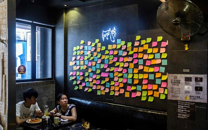 Customers sit near blank notes on a Lennon Wall inside a pro-democracy restaurant in Hong Kong - AFP
