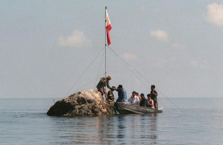 A team of Philippine Navy personnel and three congressmen land at the tiny rock of Scarborough Shoal in the South China Sea, bearing the national flag, in 1997