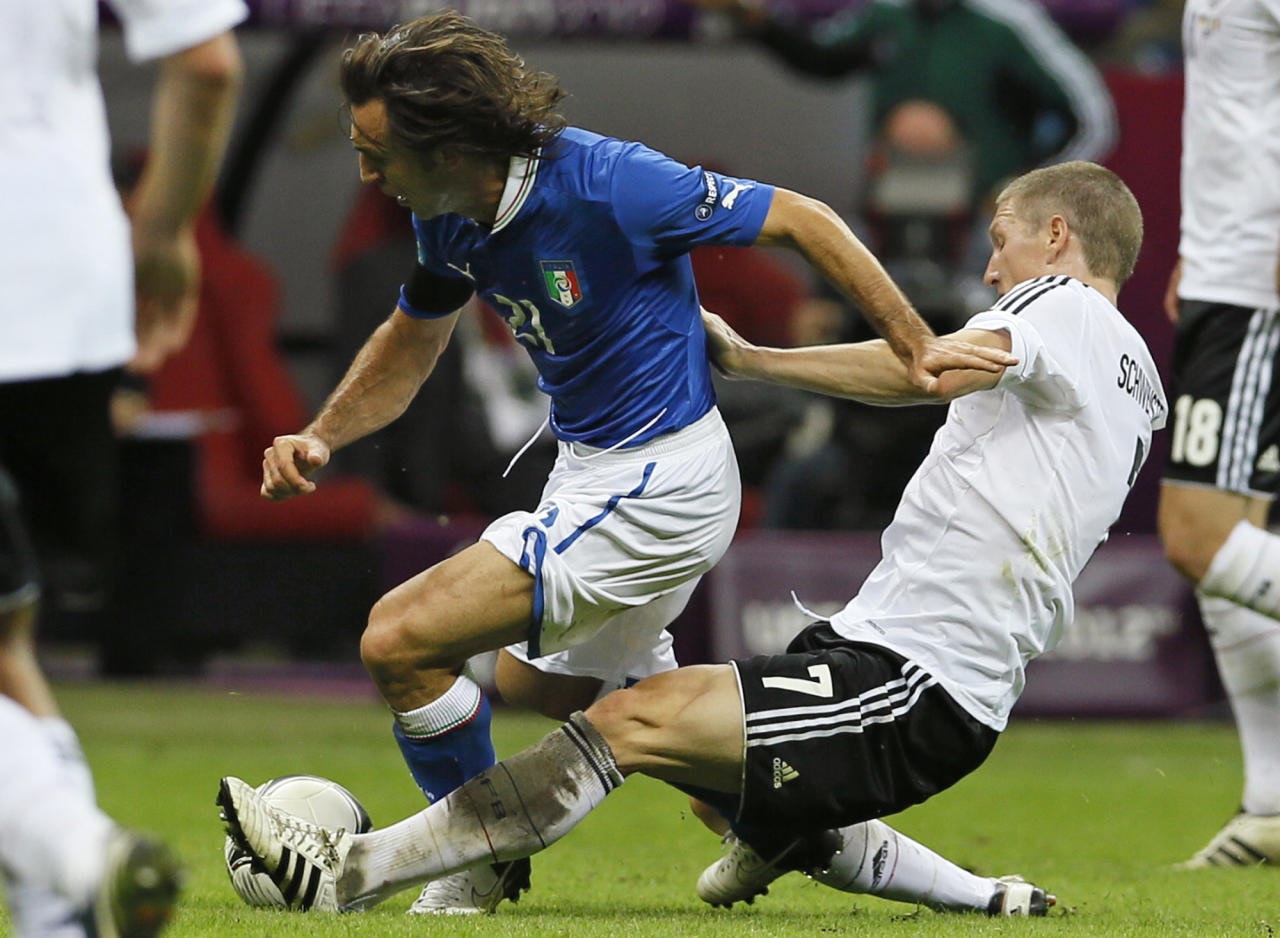 Italy's Andrea Pirlo, left, is tackled by Germany's Bastian Schweinsteiger during the Euro 2012 soccer championship semifinal match between Germany and Italy in Warsaw, Poland, Thursday, June 28, 2012. (AP Photo/Frank Augstein)