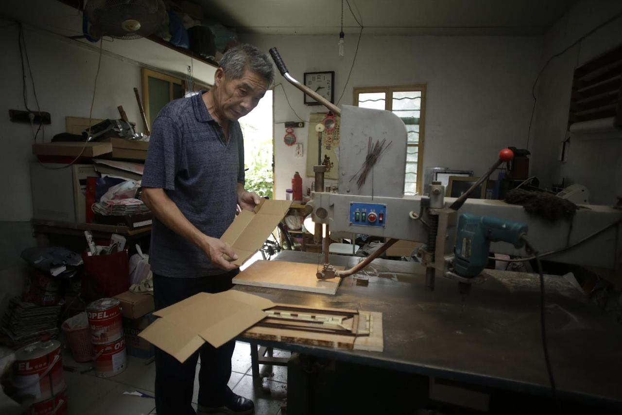"In this Sept. 9, 2013 photo, Dong Linhua, 59, works at his workshop in Shanghai. ""I heard that the authorities might postpone the age of the retirement, but I sure hope not, since I've already worked for almost 42 years,"" says Dong. (AP Photo/Eugene Hoshiko)"