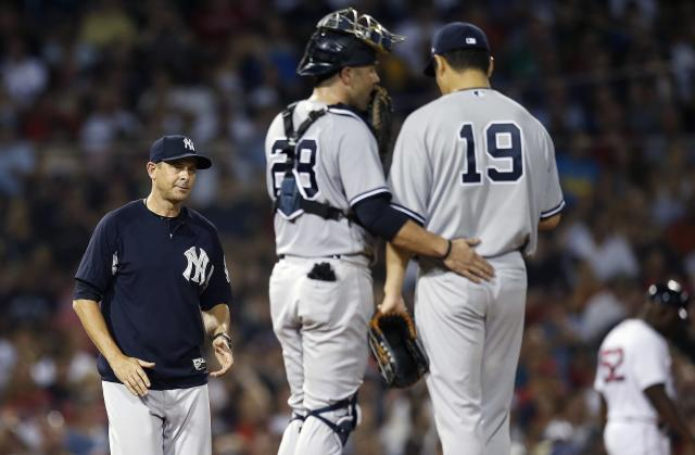 New York Yankees manager Aaron Boone, left, comes to the mound to relieve Masahiro Tanaka (19) during the fifth inning of a baseball game against the Boston Red Sox in Boston, Sunday, Aug. 5, 2018. (AP Photo/Michael Dwyer)