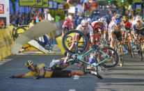 Dutch cyclist Dylan Groenewegen crashes to the ground as a bicycle is flying overhead in a major collision on the final stretch of the opening stage of the Tour de Pologne race in Katowice, Poland, on Wednesday, Aug. 5, 2020. The crash began with Groenewegen colliding with another Dutchman sprinting for the win, Fabio Jakobsen, who was hospitalized in serious condition and put into an induced coma. Jakobsen was declared the winner of the opening stage and Groenewegen was disqualified. (AP Photo/Tomasz Markowski)