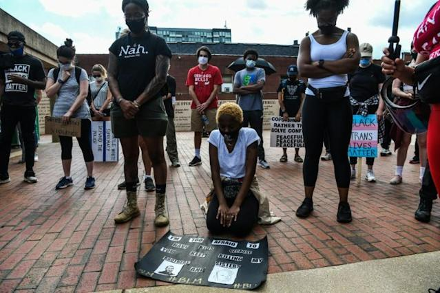 A protester kneels amidst others bowing their heads as they observe eight minutes of silence in honour of Rayshard Brooks at Martin Luther King Jr. National Urban Park in Atlanta (AFP Photo/CHANDAN KHANNA)