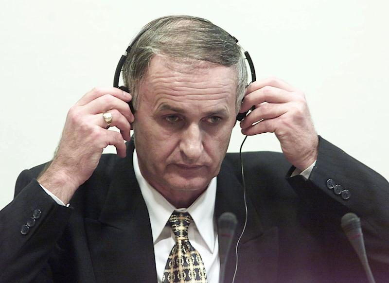 FILE - In this Thursday, Aug. 2, 2001 file photo, Bosnian Serb Gen. Radislav Krstic puts on headphones as he takes his seat in the courtroom in The Hague, Netherlands. The war criminal has been brought to Poland to serve out his sentence after he was assaulted in a British prison, a justice official said Friday March 21, 2014. Former general Radislav Krstic was convicted in 2001 and handed a 35-year prison sentence by the U.N. tribunal for the former Yugoslavia in The Hague, Netherlands, for aiding and abetting genocide over the 1995 killing of some 8,000 Muslims in Srebrenica, Bosnia. (AP Photo/Ed Oudenaarden, Pool, File)