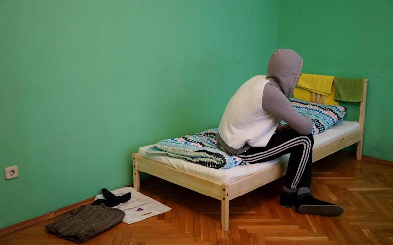 A Chechen gay man who fled persecution in Chechnya due to his sexual-orientation, sits on his bed in Moscow during an interview with AFP - Credit: NAIRA DAVLASHYAN/AFP