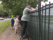 A fan uses a step-stool so he can see horse racing action above the fence at the Saratoga Race Course in Saratoga Springs, N.Y. , Thursday, July 16, 2020. A Saratoga season like no other is open, with fans barred from attending the start of the 152nd meet in track history and most likely the entire 40 days of racing. (AP Photo/John Kekis)