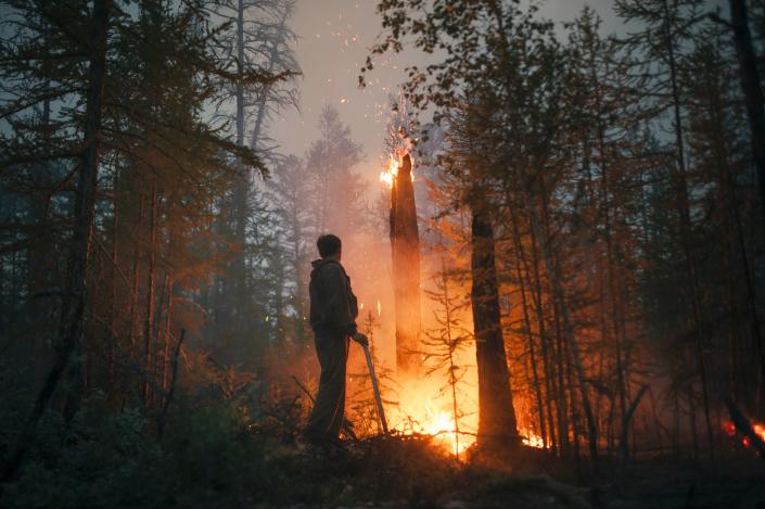 A member of volunteers crew monitors a backfire they lit to stop the fire from spreading at Gorny Ulus area west of Yakutsk, Russia, Thursday, July 22, 2021. The hardest hit area is the Sakha Republic, also known as Yakutia, in the far northeast of Russia, about 5,000 kilometers (3,200 miles) from Moscow. About 85% of all of Russia's fires are in the republic, and heavy smoke forced a temporary closure of the airport in the regional capital of Yakutsk, a city of about 280,000 people. (AP Photo/Ivan Nikiforov)
