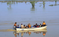 Pakistani army soldiers evacuate villagers from a flooded areas of Dadu, a district in Pakistan's southern Sindh province, Sunday, Aug. 9, 2020. Three days of heavy monsoon rains triggering flash floods killed at least dozens people in various parts of Pakistan, as troops with boats rushed to a flood-affected district in the country's southern Sindh province Sunday to evacuate people to safer places. (AP Photo/Pervez Masih)