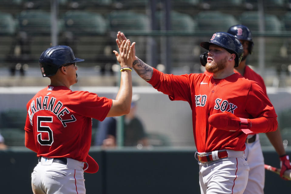 Boston Red Sox' Alex Verdugo celebrates with Enrique Hernandez (5) after scoring on a two-run double by J.D. Martinez in the fifth inning of a spring training baseball game against the Atlanta Braves on Tuesday, March 23, 2021, in North Port, Fla. (AP Photo/John Bazemore)