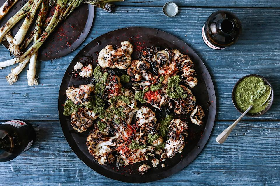 "Slicing the cauliflower into steaks from the middle helps the head stay intact as you cut. <a href=""https://www.bonappetit.com/recipe/grilled-cauliflower-steaks-scallions?mbid=synd_yahoo_rss"" rel=""nofollow noopener"" target=""_blank"" data-ylk=""slk:See recipe."" class=""link rapid-noclick-resp"">See recipe.</a>"