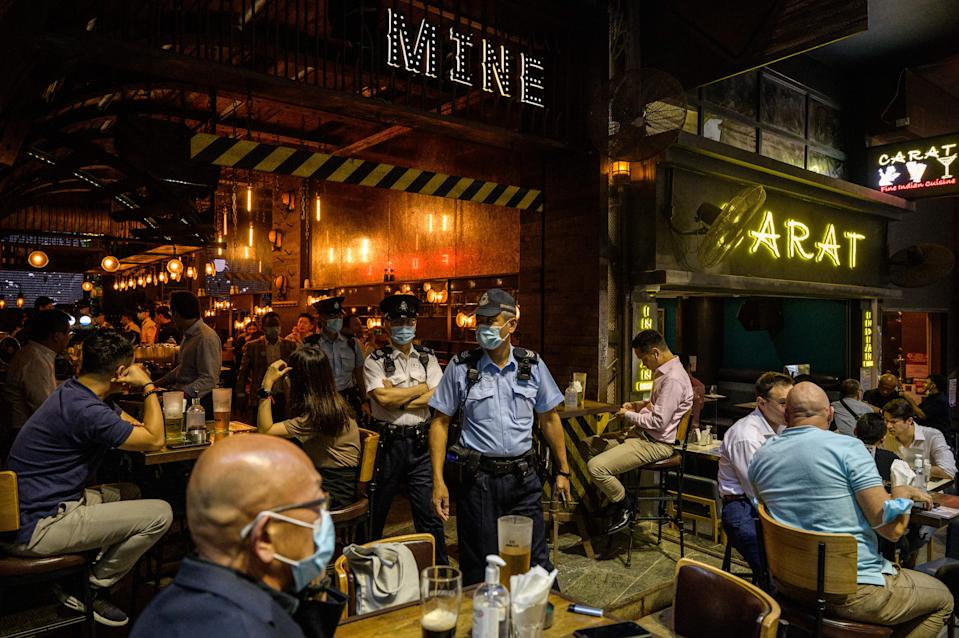 Food and Environmental Hygiene Department officers and police leave after inspecting the license of a restaurant and bar after it reopened, in Lan Kwai Fong, a popular drinking area in Hong Kong on April 29, 2021, as Covid-19 coronavirus social-distancing restrictions on restaurants and bars were eased under new vaccine bubble rules. (Photo by ANTHONY WALLACE / AFP) (Photo by ANTHONY WALLACE/AFP via Getty Images)