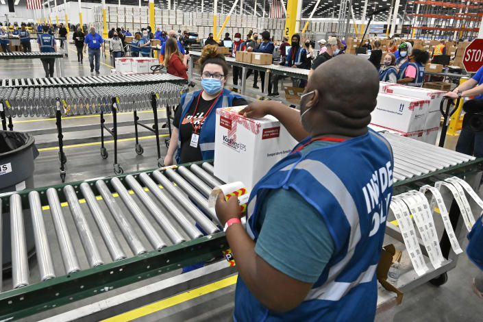 The first box containing the Johnson & Johnson COVID vaccine heads down the conveyor to an awaiting transport truck at the McKesson facility in Shepherdsville, Ky., Monday, March 1, 2021. (Timothy D. Easley/AP Photo)