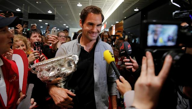 Switzerland's Roger Federer holds his Australian Open trophy as he is welcomed by fans upon his arrival at Zurich Airport, Switzerland January 30, 2018. REUTERS/Arnd Wiegmann